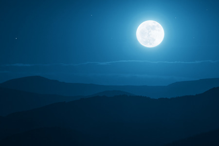 Dramatic mountain moonrise with deep blue night time sky and layered hills in the distance