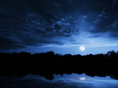 This dramatic moonrise in a deep blue sky at night is accented by highlighted clouds and beautiful, calm lake reflection Фото со стока - 26076989