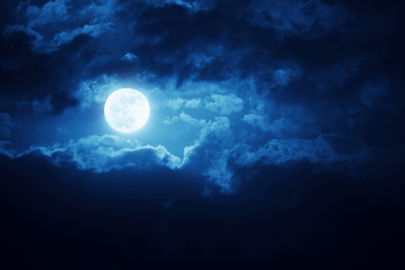 Dramatic Nighttime Clouds and Sky With Large Full Blue Moon Stock Photo