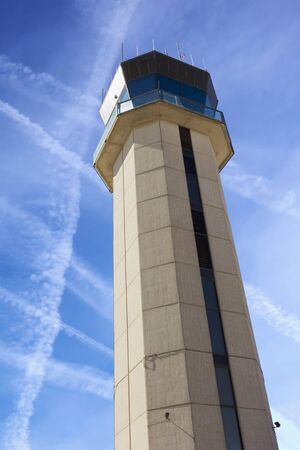 Commercial Airport Control Tower from close up perspective with sky criss-crossed by jet trails illustrating air traffic control challenges.