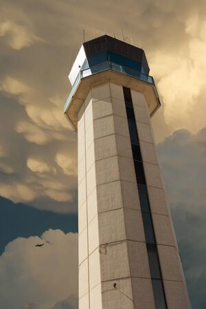 Commercial Airport Control Tower From Close Up Perspective with severe thunderstorm overhead illustrating air traffic control challenges. Фото со стока
