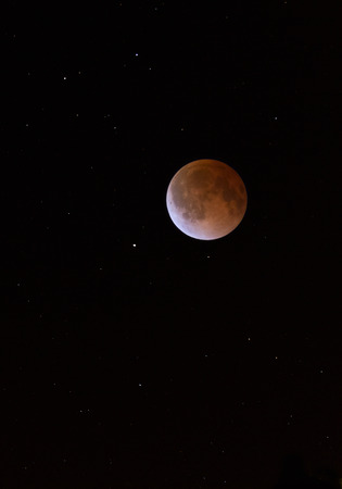 penumbra: This is a photograph of the Lunar Eclipse Blood Moon moving out of its maximum stage at 3:00am Central Time. Background star field added from same sky location later. Stock Photo