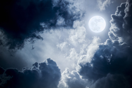 This dramatic photo illustration of a nighttime sky with brightly lit clouds and large full Blue Moon would make a great background for many uses.