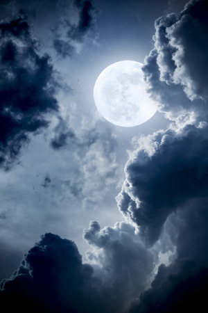 with clouds: This dramatic photo illustration of a nighttime scene with brightly lit clouds and large full Blue Moon would make a great background for many uses.