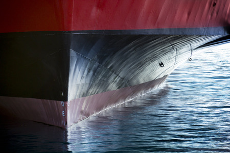 A beautiful horizontal graphic view of the bow of a large ship in port. It would make a great cover image of anything involving international shipping transportation industrial cargo or ferry