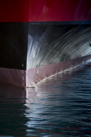 involving: A beautifull vertical graphic view of the bow of a large ship in port. It would make a great cover image of anything involving international shipping transportation industrial cargo or ferry.
