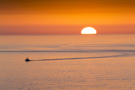 This fishing boat heads home from fishing in front of a beautiful sunset at Clearwater Beach Florida in the Gulf of Mexico. Stock Photo