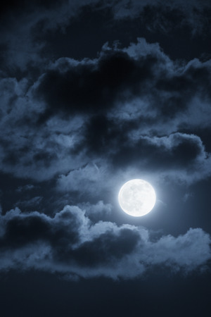 This dramatic photo illustration of a nighttime scene with brightly lit clouds and large full Blue Moon would make a great background for many uses.