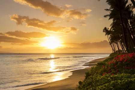 Beautiful warm tropical sunset on the white sands of Kaanapali Beach in Maui Hawaii. A fabulous destination for vacation and travel. Stock Photo
