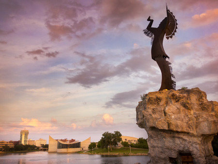 A warm beautiful sunset along the Arkansas River in Wichita Kansas. The Keeper of the Plains in the foreground stands more than 70 feet tall including its promontory. Stock Photo