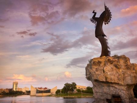 Een warme prachtige zonsondergang langs de rivier de Arkansas in Wichita Kansas. De bewaarder van de Plains op de voorgrond staat meer dan 70 voet lang met inbegrip van de kaap.