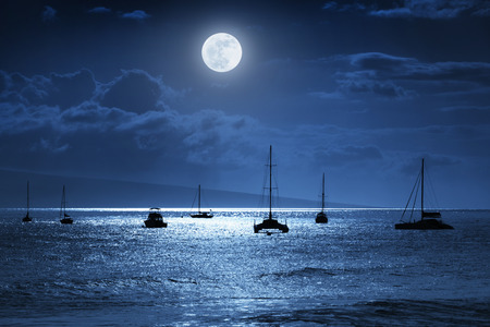 This dramatic photo illustration of a nighttime sky over a calm ocean scene in Maui Hawaii with brightly lit clouds a large full Blue Moon calm waves and sparkling reflections would make a great background for many travel or vacation uses. Archivio Fotografico