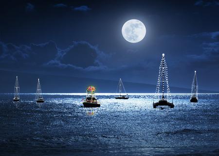 Este ejemplo de la foto muestra una escena tropical del día de fiesta caliente con barcos de luna llena decorados con luces y una palmera como un árbol de Navidad. Foto de archivo