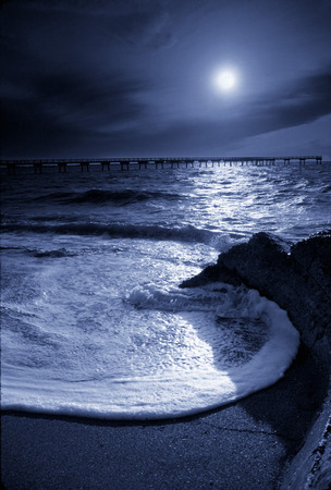 Beautiful night time photo illustration of a moonlit circular ocean wave and pier