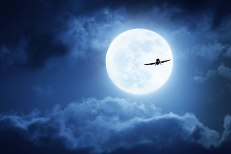 Dramatic photo illustration of a nighttime sky with brightly lit clouds and large, full, Blue Moon silhouetting a commercial aircraft would make a great background for travel or tourism.