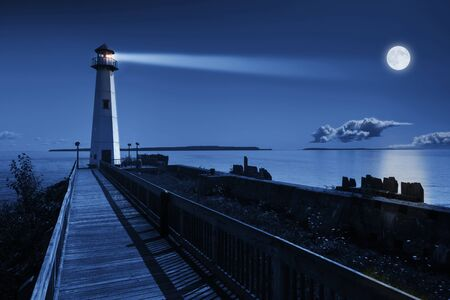 This is a beautiful photo illustration of a dramatic night time scene of a blue moonrise in a clear sky on a ocean pier with a brightly lit lighthouse beacon and calm ocean waters.