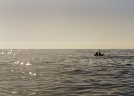 backlighting: Backlighting of a couple paddling with kayak at sunrise on a completely calm sea  Stock Photo