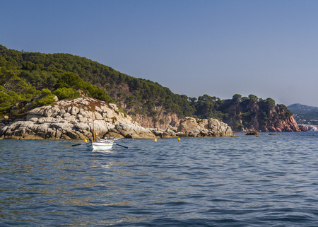 barque: A traditional fisher paddling with his barque in a rocky cove of the Costa Brava