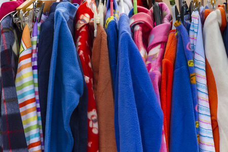 Detail of a colorful display of robes and other clothing at a flea market photo