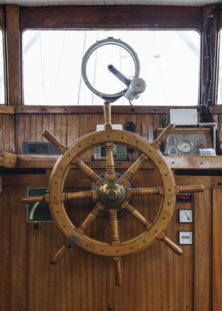 wheelhouse: Wheelhouse, helm wheel and control panels in an old wooden boat  Front view