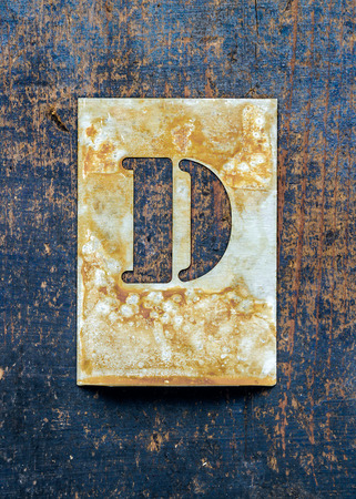 printery: Metal typography over a weathered wood background showing the alphabet letter  D  Stock Photo