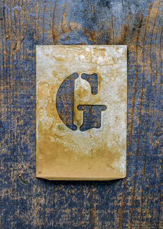 fount: Metal typography over a weathered wood background showing the alphabet letter  G