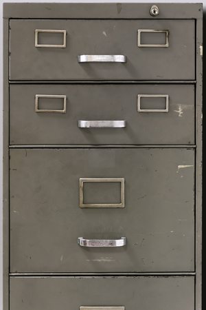 Front view of the drawers of metal filing cabinet of an old office