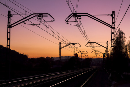remoteness: Perspective of the catenary and the railroad tracks, backlit, at dusk, with a purple sky