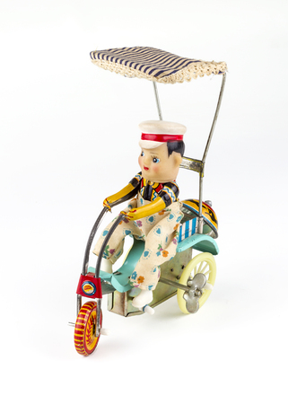 antique tricycle: Antique brass doll: a child on a tricycle Stock Photo