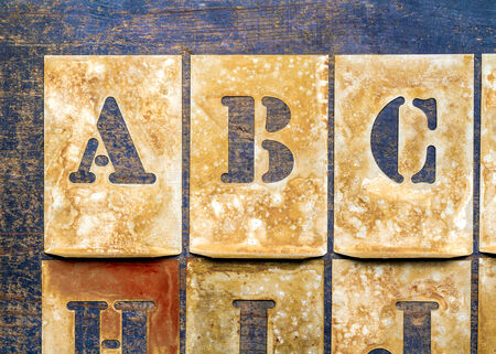 printery: Metal lettering over a weathered wood background showing letters of the alphabet \\\ABC\\\