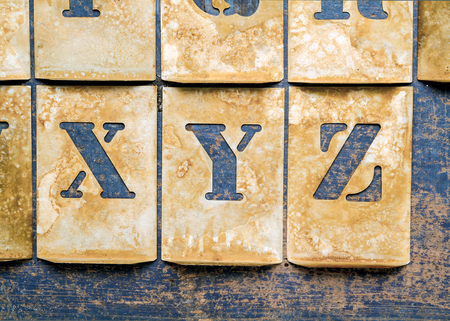 Metal lettering over a weathered wood background showing letters of the alphabet \\\XYZ\\\