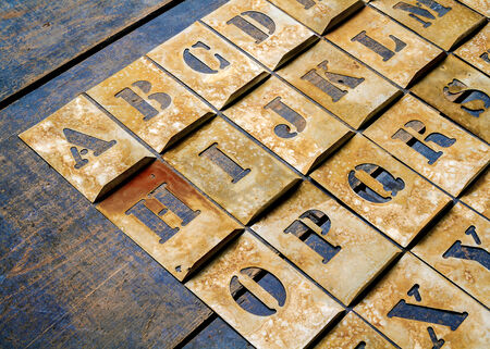 printery: Metal lettering over a weathered wood background showing letters of the alphabet.