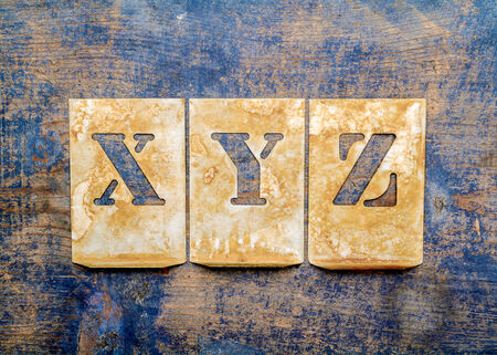 xyz: Metal lettering over a weathered wood background showing letters of the alphabet XYZ
