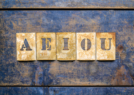 printery: Metal lettering over a weathered wood background showing vowels AEIOU