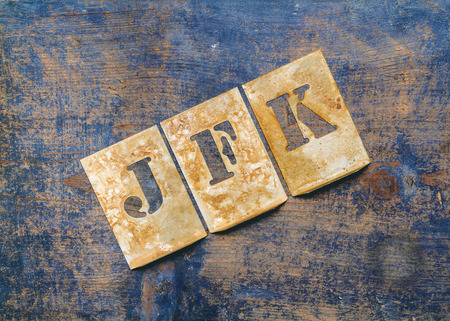 Metal lettering over a weathered wood background showing the initials of John Fitzgerald Kennedy \JFK\ Stock Photo