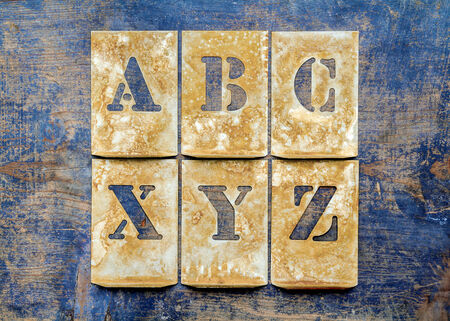 xyz: Metal lettering over a weathered wood background showing letters of the alphabet \ABC\ and \XYZ\ Stock Photo