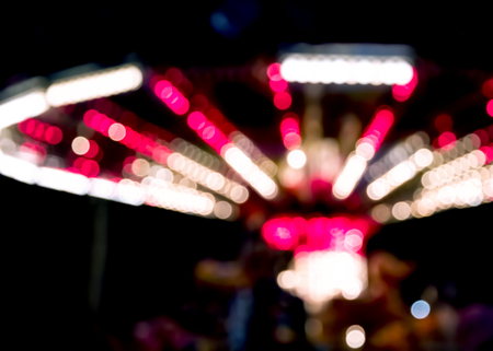 fastness: Blurred lights of a fairground carousel against a black background
