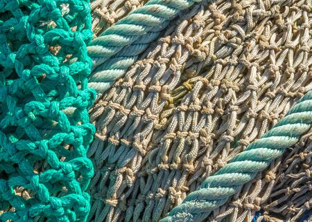muddle: Close-up of fishing nets stacked in the harbor, paying particular attention to the colors, textures, materials, details, knots, etc.