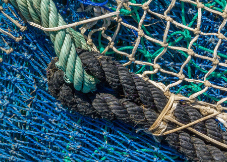 trawl: Close-up of fishing nets stacked in the harbor, paying particular attention to the colors, textures, materials, details, knots, etc.