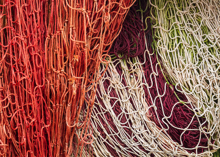 disordered: Close-up of fishing nets stacked in the harbor, paying particular attention to the colors, textures, materials, details, knots, etc.