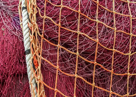 spearfishing: Close-up of fishing nets stacked in the harbor, paying particular attention to the colors, textures, materials, details, knots, etc.