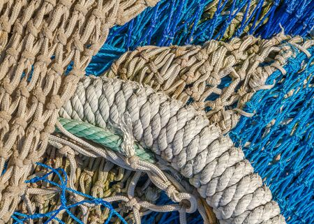 tether: Close-up of fishing nets stacked in the harbor, paying particular attention to the colors, textures, materials, details, knots, etc.