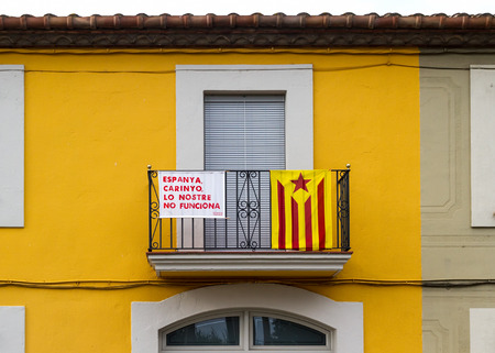 photojournalism: Barcelona, Catalonia - September 11, 2013 - On a balcony, a starry flag the Catalan secessionist emblem and a placard saying sarcastically Spain, honey, ours doesnt work