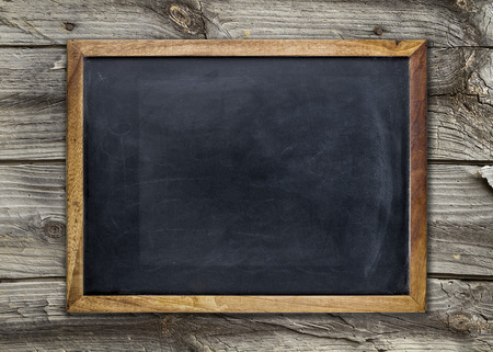 blackboard background: Front view of a blank blackboard over a weathered wooden surface