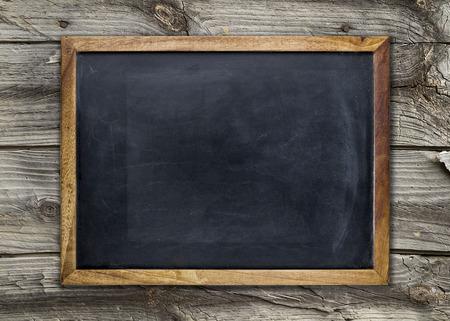 blackboard: Vista frontal de una pizarra en blanco sobre una superficie de madera degradada