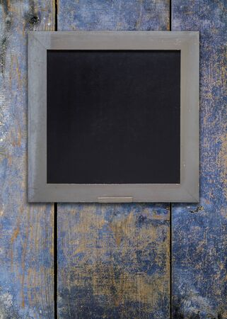 retro frame: Front view, upright format, of a blank blackboard over a weathered wooden surface