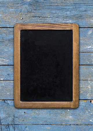 upright format: Front view, upright format, of a blank blackboard over a weathered wooden surface