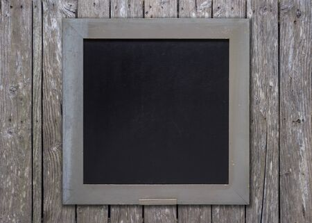forefront: Front view of a blank blackboard over a weathered wooden surface