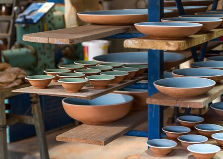 craftwork: Dishes and bowls sorted in a ceramist workshop Stock Photo