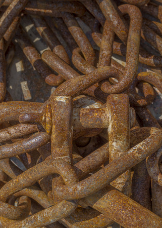 fishing gear: Rusted chains of a trawl fishing gear stacked in the harbor. Stock Photo